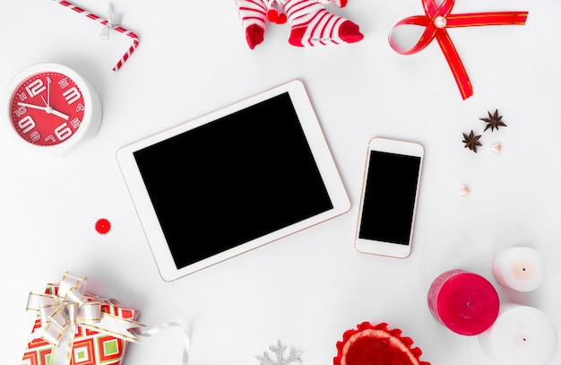 モックアップのための孤立した白い画面を備えたテーブル上のタブレットスマートフォンモバイルディスプレイ