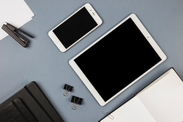 Tablet and smartphone with notebook on grey table