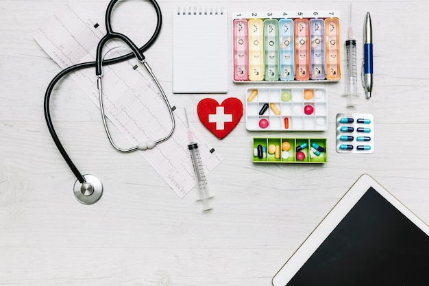 Tablet and stethoscope near pills organizers