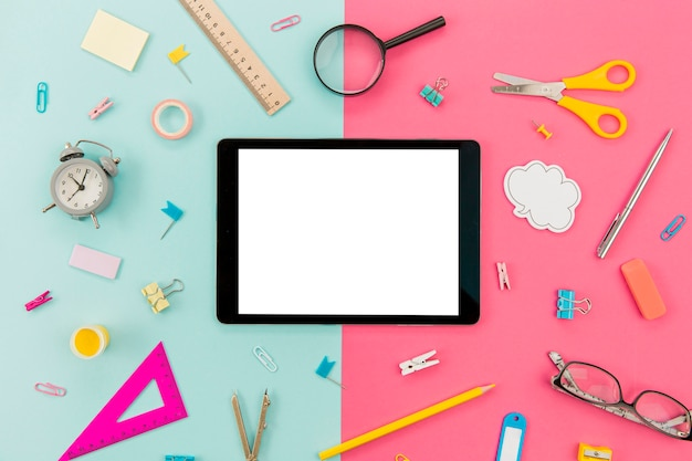 Tablet surrounded by stationery supplies on the table