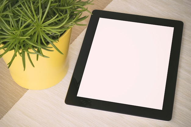 Tablet over a table with plant
