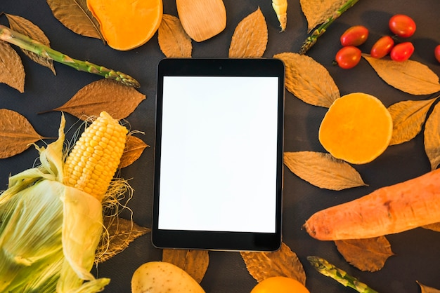 Tablet on table with vegetables