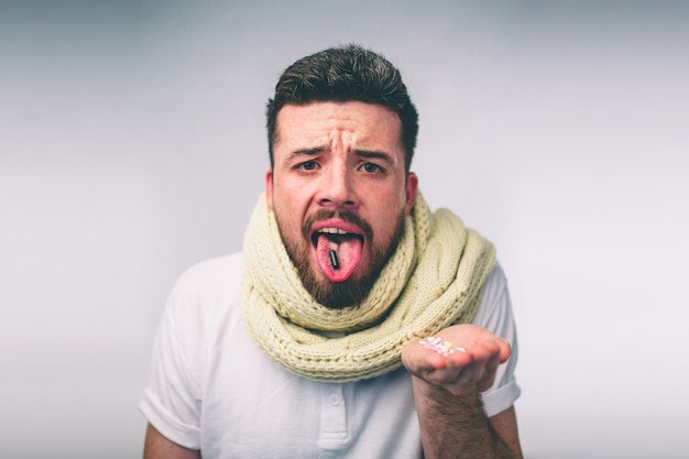 Tablet on the tongue of a bearded guy