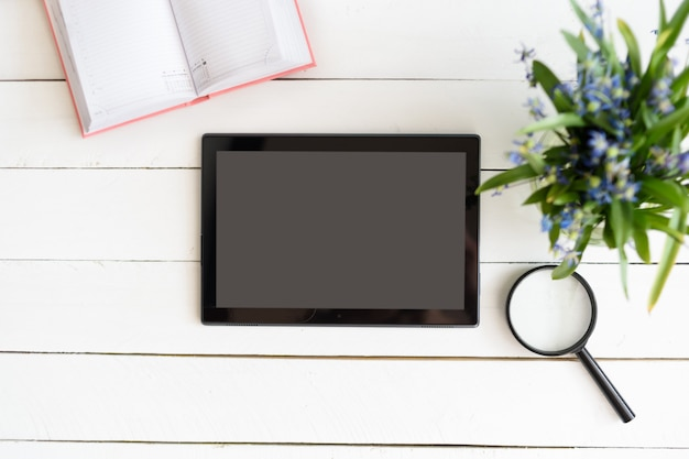 Tablet with black empty screen. notebook, magnifier and flowers on table
