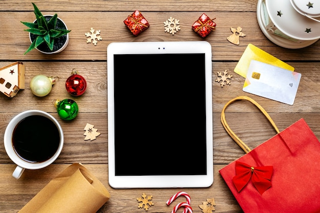 Tablet with black screen, cup of coffee, debit card, xmas decor, snowflakes on wooden table