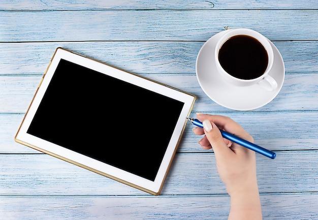 나무 배경에 커피 한잔과 스타일러스로 손 근처 검은 화면 태블릿
