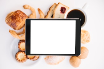 Tablet with blank screen above coffee with bakery
