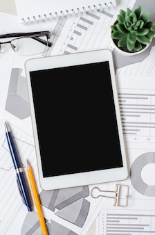 Tablet with a blank screen on the background of charts and graphs with pencils, glasses and a plant