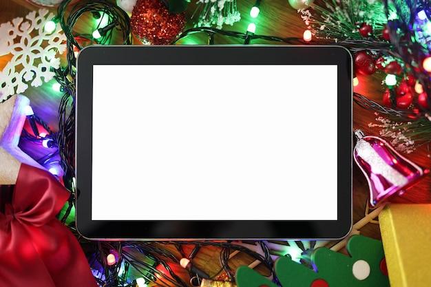Таблетка с пустым экраном лежит на столе на фоне новогодних украшений