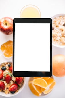Tablet with blank screen above oatmeal and fruits