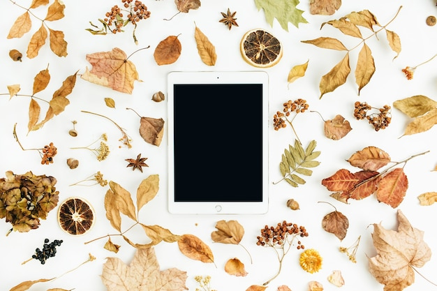 Tablet with blank screen with dry fall autumn leaves, petals and oranges on white surface