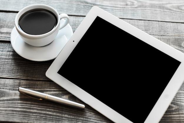Таблетка с кофе и металлической ручкой на деревянном столе