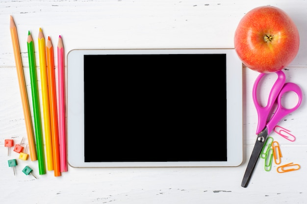 Tablet with an empty screen and office supplies on a white wooden background. concept app for school children or online learning for children. copy space