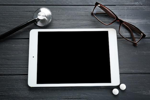 나무 배경에 안경 태블릿