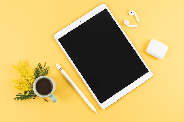 Tablet with headphones and pencil on yellow background. top view. copy space.