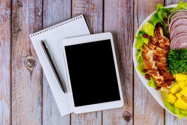 木製のテーブルに健康サラダを搭載したタブレットします。