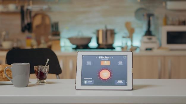 誰もいないキッチンのテーブルにインテリジェントなソフトウェアを配置し、ハイテクアプリケーションで光を制御するタブレット。空の家の自動化システムのスマートホームアプリとメモ帳