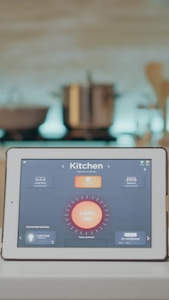 Tablet with intelligent software placed on table in kitchen with nobody in