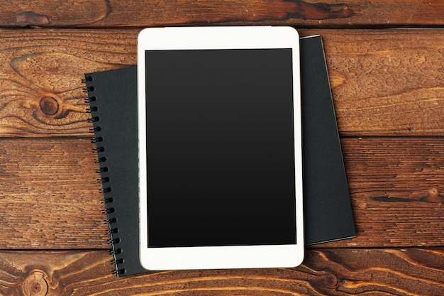 Tablet with notepad on wooden