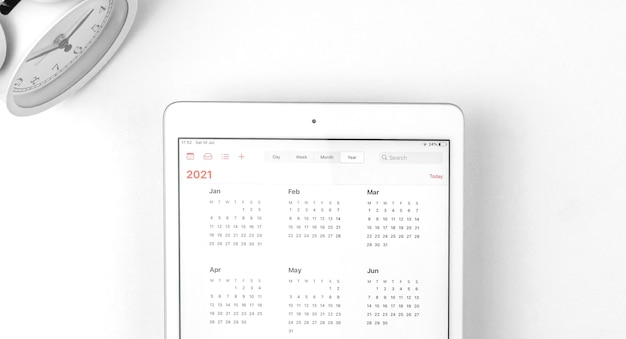 캘린더 2021이 열려 있는 태블릿, 알람 시계가 있는 흰색 배경 작업 공간, 비즈니스 컨셉 사진