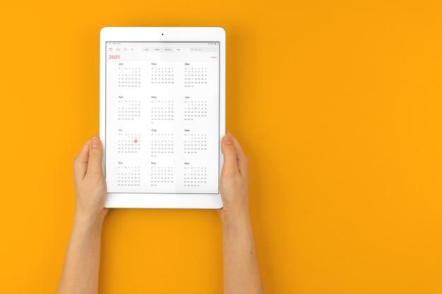 캘린더 2021이 열린 태블릿, 여성의 손은 복사 공간이 있는 노란색 밝은 바탕 화면에 태블릿을 들고 있습니다.