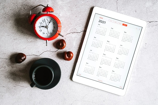A tablet with an open calendar for 2021 year, a cup of coffee, chestnuts and a red alarm clock