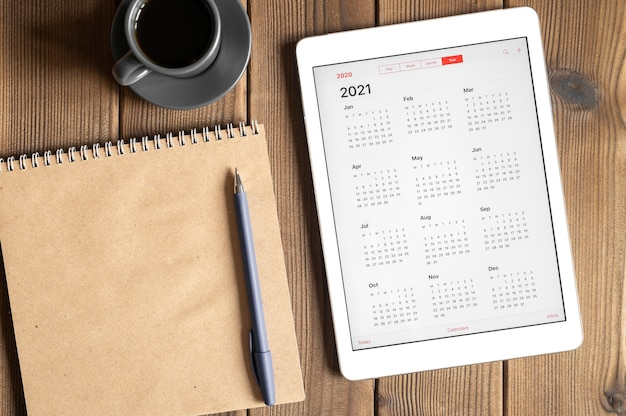 A tablet with an open calendar for 2021 year, a cup of coffee and a craft paper notebook