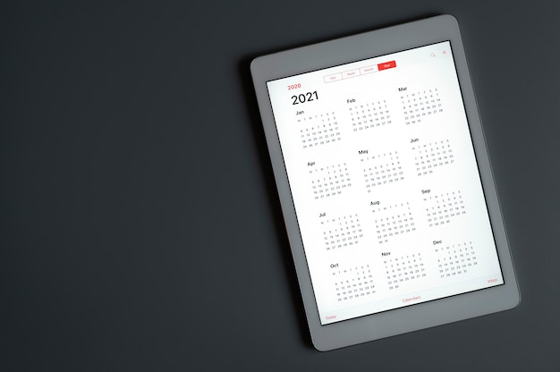 A tablet with an open calendar for 2021 year on a dark gray