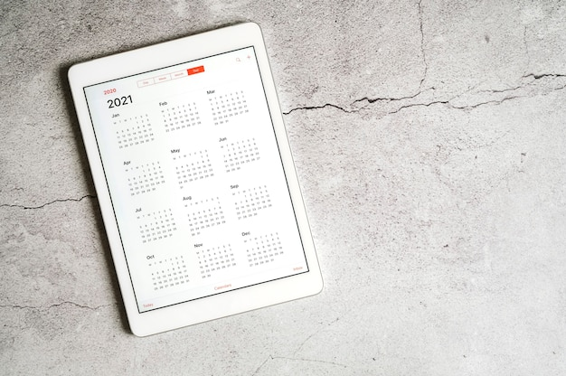 A tablet with an open calendar for 2021 year on a gray concrete table