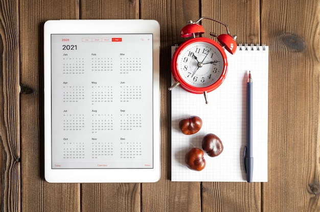 A tablet with an open calendar for 2021 year, a red alarm clock, chestnuts, and a spring notebook with a pen on a wooden boards table background