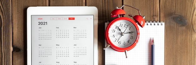 A tablet with an open calendar for 2021 year, a red alarm clock, chestnuts, and a spring notebook with a pen on a wooden boards table background.