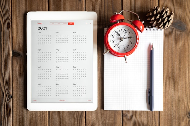 A tablet with an open calendar for 2021 year, a red alarm clock, a pine cone, and a spring notebook with a pen on a wooden boards table background