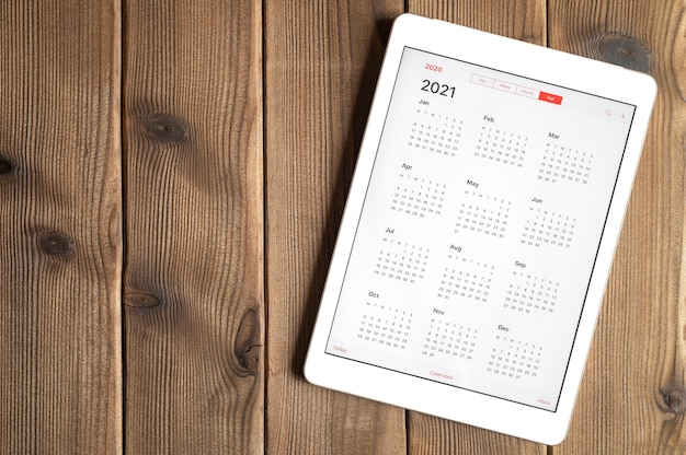 A tablet with an open calendar for 2021 year on a wooden boards table background. space for text