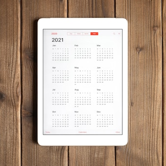 A tablet with an open calendar for 2021 year on a wooden boards table background. square