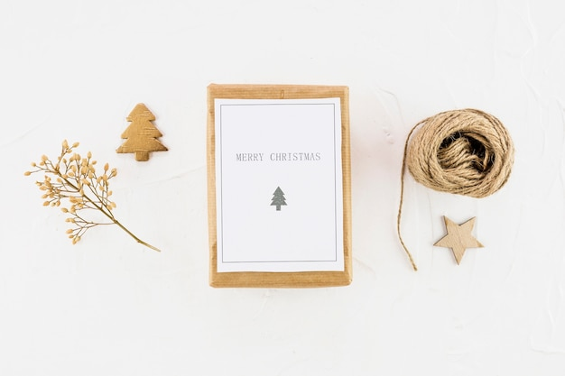 Tablet with paper between decorative fir tree, star and threads