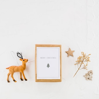 Tablet with paper between decorative fir tree, star and toy deer