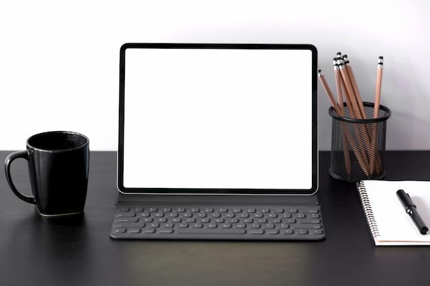 Tablet with smart keyboard case with blank screen on dark wood table