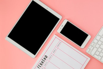 Tablet with smartphone and notebook on pink table