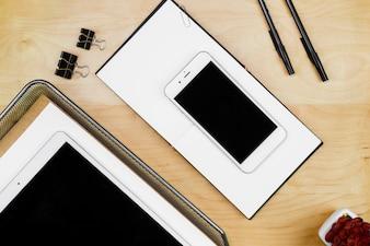 木製のテーブルの上にスマートフォンを搭載したタブレットします。