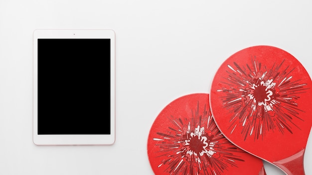 Tablet with tennis rackets on light background