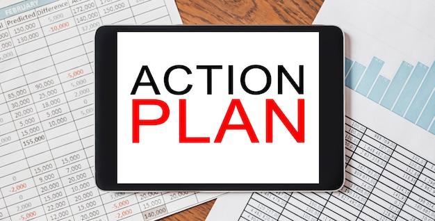 ドキュメント、レポート、グラフを備えたデスクトップ上のテキストアクションプランを備えたタブレット。ビジネスと金融の概念