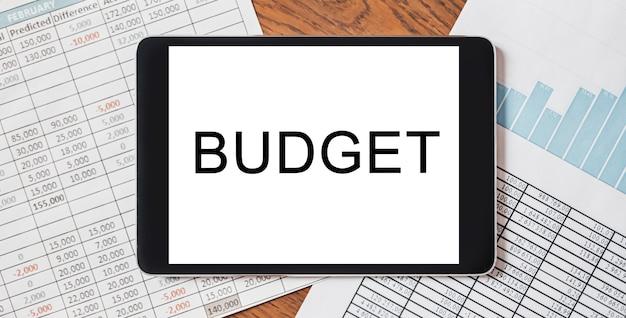 ドキュメント、レポート、グラフを備えたデスクトップ上のテキスト予算付きタブレット。ビジネスと金融の概念