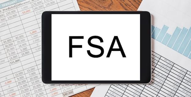 ドキュメント、レポート、グラフを備えたデスクトップ上のテキストfsaを備えたタブレット。ビジネスと金融の概念