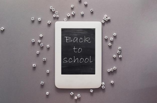 Табличка с надписью обратно в школу на фоне графитовой бумаги алфавит лежит вокруг ...