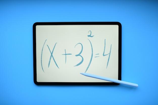 鉛筆と青いテーブルに数式の碑文とタブレット