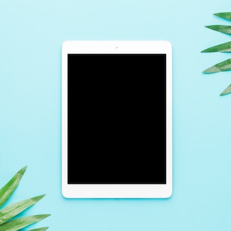 Tablet with tropical leaves on light background