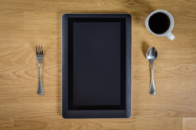 Tablet over wood table with spoon, fork and coffee cup