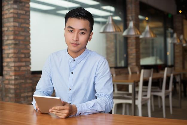 Дружественные человек сидит в кафе таблице с tablet