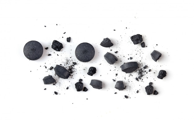 Tablets activated charcoal and powder on white.