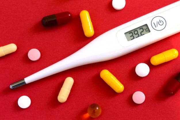 Таблетки и термометр на красном фоне